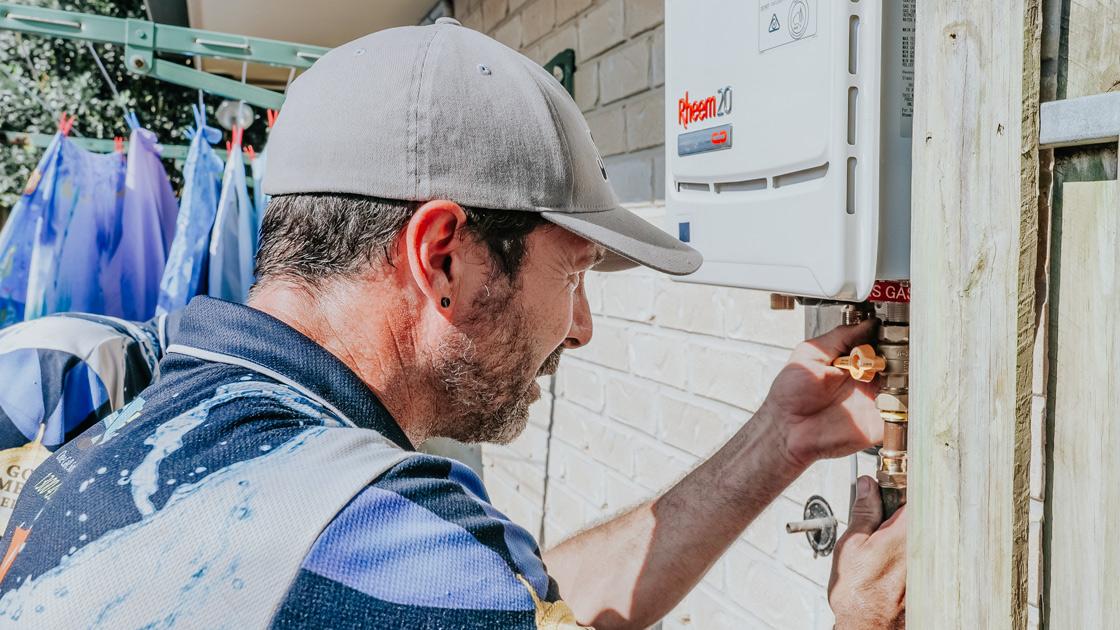 Plumber repairing hot water system in Brisbane